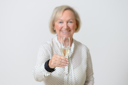 socialising: Senior woman toasting with champagne raising her flute to the camera with a happy smile as she celebrates a special event