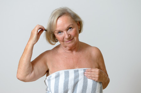 strapless: Senior woman combing her blond hair with a comb head and shoulders on a neutral gray background