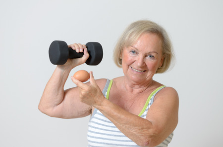 muscle toning: Fit healthy senior lady holding a dumbbell strong and egg in her hands in a conceptual image of Health Fitness and Diet for a healthy lifestyle Stock Photo