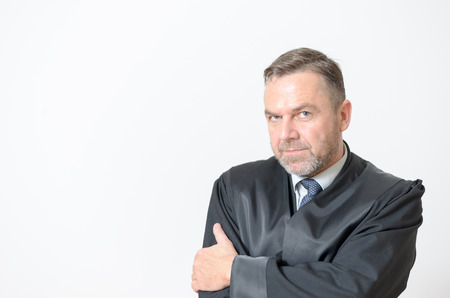 speculative: Confident businessman standing with folded arms and a serious expression giving the camera a penetrating speculative look head and shoulders with copyspace