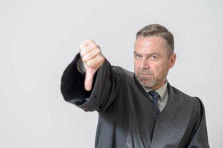 counsel: Businessman giving a thumbs down gesture to show he disagrees a failure or voting down on something with a stern expression