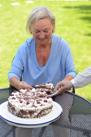 devouring: Elderly lady enjoying a slice of freshly baked creamy chocolate cake as she relaxes at a table outdoors in her garden