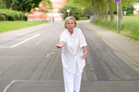 mentally ill: Portrait of a Middle Aged Blond Woman in White Outfit All walking at the street alone in friendly facial expression. Stock Photo