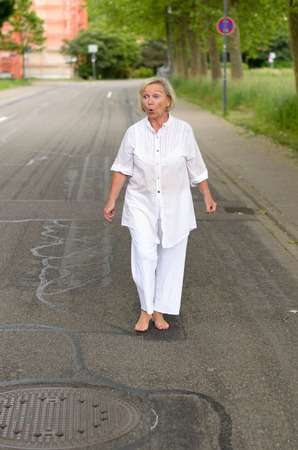 mentally ill: Full Length Shot of a Middle Aged Blond Woman at the Street Wearing All White Clothes with Bare Feet Showing Shocked Facial Expression While Looking Into Distance.