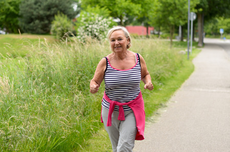 cardiovascular workout: Healthy Middle Aged Blond Woman in casual wear jogging at the Street Alone While Smiling at the Camera.