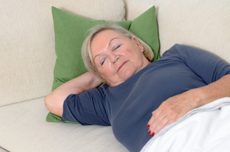 convalescence: Close up Middle Aged Blond Woman Resting on Couch with Pillow and Blanket at the Living Room.