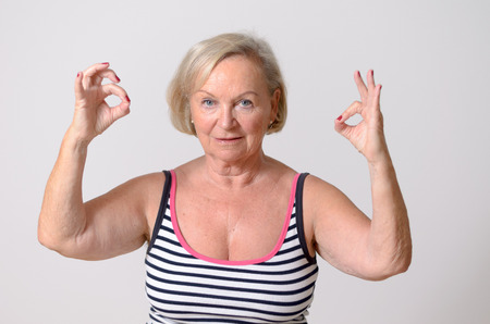commendation: Portrait of a Middle Aged Blond Woman in Casual Striped Shirt Showing Two Okay Handsigns While Looking at the Camera. Isolated on Light Gray Wall background.
