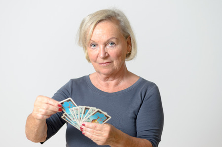 adivino: Grave mujer de mediana edad sosteniendo Fan de cartas del Tarot, mientras que mirando a la c�mara sobre fondo gris claro Muro.