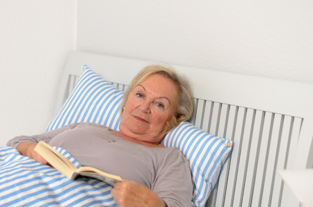 novel: Middle Aged Woman Holding a Novel Book While Lying on her Bed and Looking at the Camera.