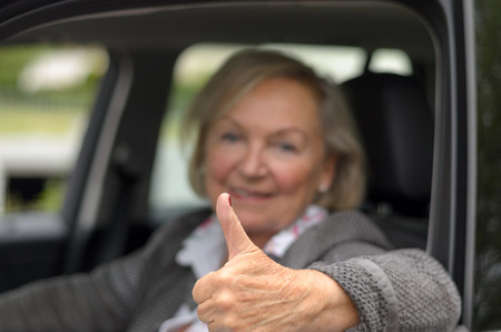 people looking up: Elderly woman sitting in a car with thumb up while looking to the camera