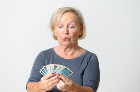 adivino: Grave mujer de mediana edad sosteniendo Fan de cartas del Tarot, mientras que mirando en el fondo de las tarjetas contra luz gris Muro.