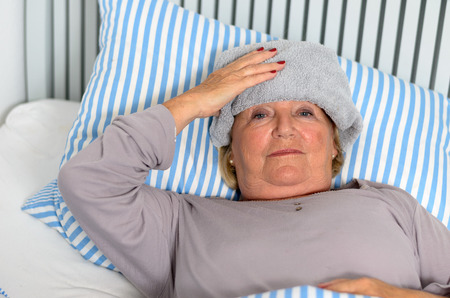 recuperating: Sick Middle Aged Woman Lying Down on Bed with Towel on the Forehead While Looking up in Pensive Facial Expression.