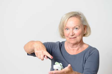 oldage: Close up Adult Blond Woman Pointing at Crumpled Money on her otherhand While Looking at the Camera Isolated on Light Gray Background. Stock Photo