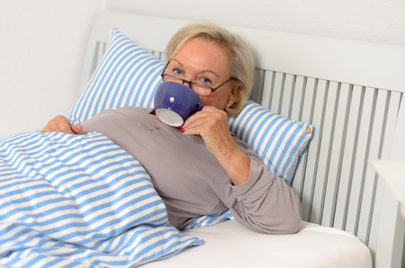 convalescence: Sick Middle Aged Blond Woman Lying on her bed holding cup of tea While Looking at the Camera.