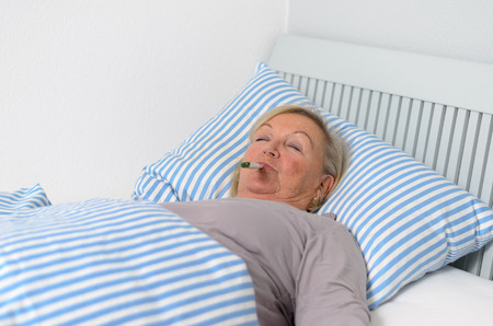 recuperating: Sick Middle Aged Woman Lying Down on Bed with Thermometer in Mouth While Looking up in Pensive Facial Expression.