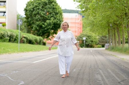 senile: Portrait of a Middle Aged Blond Woman in White Outfit All walking at the street alone in Serious Facial Expression. Stock Photo