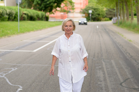 mentally ill: Portrait of a Middle Aged Blond Woman in White Outfit All walking at the street alone in Serious Facial Expression. Stock Photo