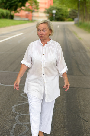 oldage: Portrait of a Middle Aged Blond Woman in White Outfit All walking at the street alone in Serious Facial Expression. Stock Photo