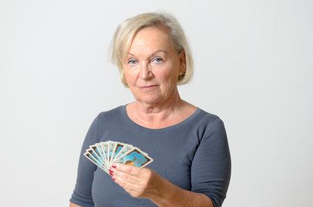 adivino: Grave mujer de mediana edad sosteniendo Fan de cartas del Tarot, mientras que mirando a la cámara sobre fondo gris claro Muro.