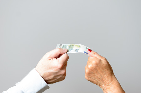 payoff: Close up Two Bare Hands of Man and Woman Holding the Edges of a Euro Bill Against Light Gray Wall Background.