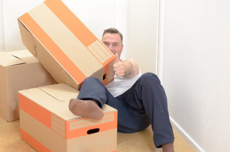removals: Man moving home relaxing amongst a collection of cardboard boxes packed with his belongings lying on the floor giving a thumbs up of success and approval Stock Photo