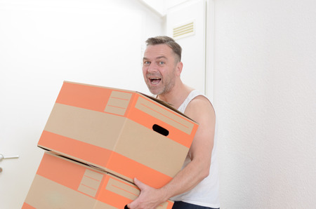 belongings: Happy friendly middleaged one moving home carrying two cardboard cartons packed with his personal belongings Stock Photo
