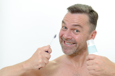 Charismatic man looking at the camera with a comic expression with a toothbrush and toothpaste in his hand Stock Photo