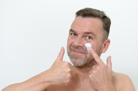 ageing: Middle-aged man applying moisturizer to his skin to ward off the signs of ageing in a skincare and pampering concept, head shot on grey