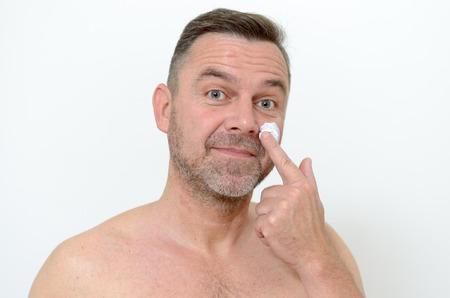 mimos: Hombre de mediana edad de aplicar crema hidratante para la piel para protegerse de los signos de envejecimiento en un concepto de cuidado de la piel y cuidado del cuerpo, la cabeza un disparo en gris