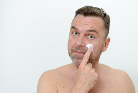 pampering: Middleaged one applying moisturizer to his skin to ward off the signs of aging in a pampering skincare and concept headshot on gray