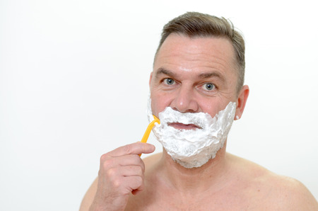 lather: Middleaged man shaving his beard with a razor and lather from shaving cream covering his face isolated on white