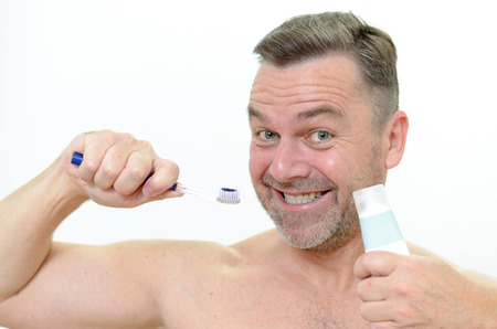 charismatic: Charismatic man looking at the camera with a comic expression with a toothbrush and toothpaste in his hand Stock Photo