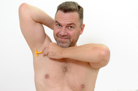 underarm: Middleage man with unshaven stubble shaving his underarm with a razor on white Stock Photo