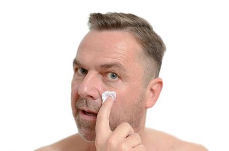 mimos: Uno de mediana edad de aplicar la crema hidratante a la piel para protegerse de los signos de la edad en un cuidado de la piel cuidado del cuerpo y el concepto de tiro en la cabeza en blanco