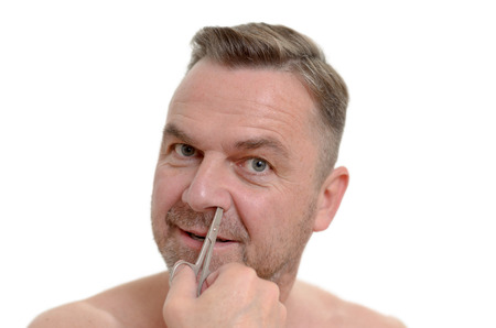unshaven: Unshaven one middleaged plucking his nose hairs with tweezers in a personal hygiene and grooming concept headshot isolated on white