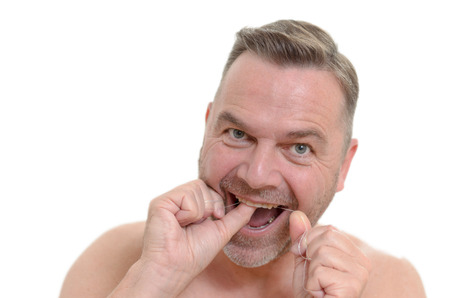 build up: Man flossing between his teeth with dental floss to prevent plaque build up and tooth decay in on oral hygiene healthcare and dentistry concept