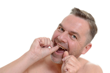 flossing: Man flossing between his teeth with dental floss to prevent plaque build up and tooth decay in on oral hygiene healthcare and dentistry concept
