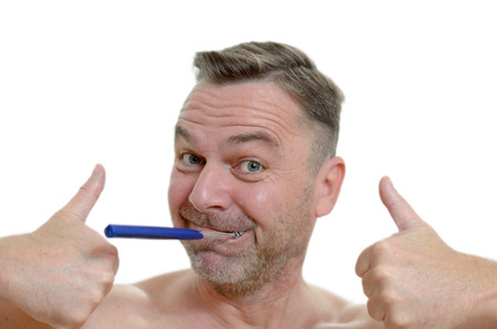 charismatic: Charismatic man cleaning his teeth looking at the camera with a comic expression with the toothbrush in his mouth as he gives a double thumbs gesture of approval Stock Photo