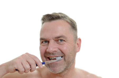 charismatic: Charismatic man cleaning his teeth looking at the camera with a comic expression with the toothbrush in his mouth