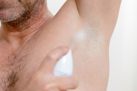 deodorant: Man using a deodorant because to avoid odor