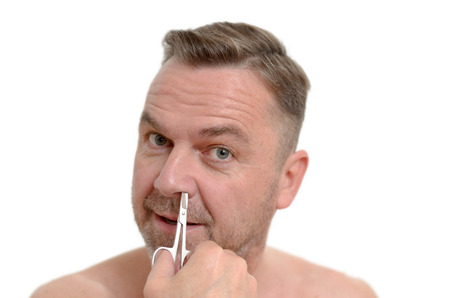 plucking: Unshaven one middleaged plucking his nose hairs with tweezers in a personal hygiene and grooming concept headshot isolated on white