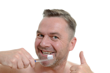 charismatic: Charismatic man cleaning his teeth looking at the camera with a comic expression with the toothbrush in his mouth as he gives a thumb up gesture of approval