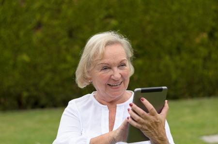 lawn chair: Senior serene woman wearing white shirt and sitting on a chair on the green lawn of the garden while using a wireless tablet PC in a black hot day of summer