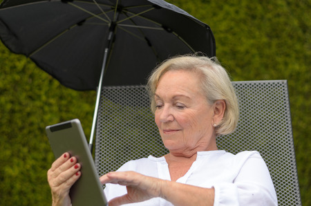 lieing: Senior serene woman wearing white shirt and lieing on a camp bed on the green lawn of the garden while using a wireless tablet PC black and showing thumb up in a hot day of summer