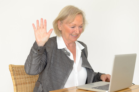 to interfere: Active blond senior woman with formal clothes and friendly smile showing hand up while sitting at desk in front of a silver laptop