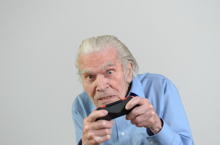 funny elderly: Funny elderly man or grandfather playing a video game on console portrait with copyspace on gray