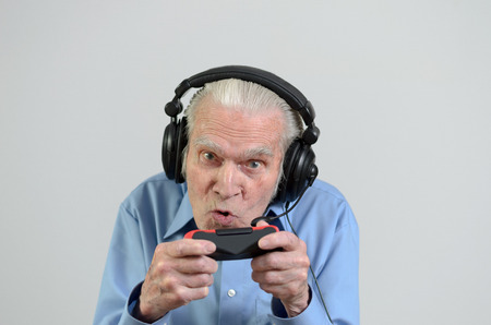 funny elderly: Funny elderly man or grandfather using black headset with headphones and microphone while playing a video game on console portrait with copyspace on gray