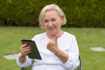lawn chair: Senior serene woman wearing white shirt and sitting on a chair on the green lawn of the garden while using a wireless tablet PC black and showing thumb up in a hot day of summer Stock Photo