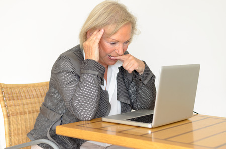 Active blond senior woman with formal clothes sitting thoughtful at a  desk in front of a silver laptop Banco de Imagens