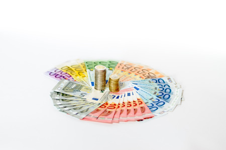 denominations: Artistic arrangement of Euro notes and coins with Euro banknotes of different denominations arranged in a fanned circle around the stacked coins on a white background in a conceptual financial image